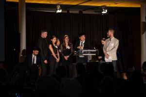 Group of young people making acceptance speech at a podium on stage