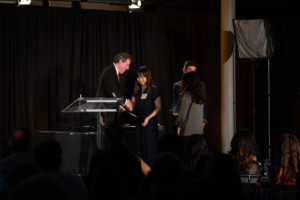 Young lady shakes presenters hand at a podium on stage
