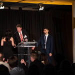 Young lady shakes presenter's hand at a podium on stage