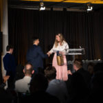 Young lady shaking host's hand at a podium on stage