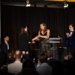 One lady presenting award to another at a podium on stage