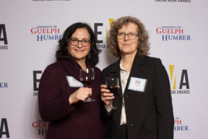 Two older ladies smiling, holding glass of wine standing on red carpet in front of white banner background