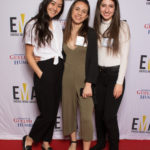 Three younger ladies smiling, dressed business casual standing on red carpet in front of white banner background