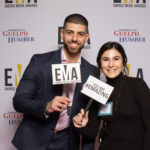 "Two young adults dressed business casual on red carpet holding signs that read ""EMAs"" and ""You are #EMAZING"""