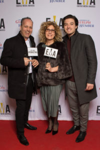 """Three people dressed business casual on red carpet holding signs that read """"EMAs"""" and """"You are #EMAZING"""""""
