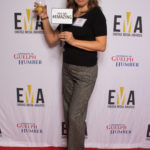 "One lady dressed business casual on red carpet holding a sign that reads ""You are #EMAZING"""