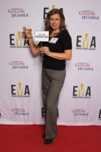 """One lady dressed business casual on red carpet holding a sign that reads """"You are #EMAZING"""""""