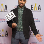 "One male dressed business casual standing on red carpet holding sign that read ""EMA"""