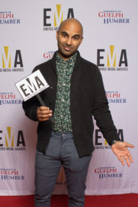 """One male dressed business casual standing on red carpet holding sign that read """"EMA"""""""