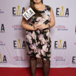 "One lady dressed business casual on red carpet holding a small sign that reads""EMA"""