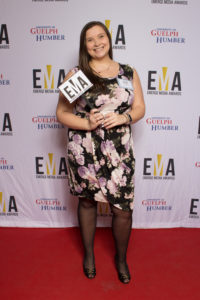 """One lady dressed business casual on red carpet holding a small sign that reads""""EMA"""""""
