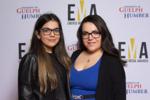 Two young ladies dressed business casual on red carpet
