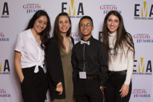 Four young adults dressed business casual on red carpet