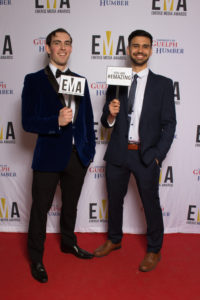 "Two young males dressed in tuxes on red carpet holding small signs that reads ""EMA"" and ""You are #EMAZING"""