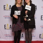 "Two ladies dressed business casual on red carpet holding small signs that read ""EMA"" and ""You are #EMAZING"""