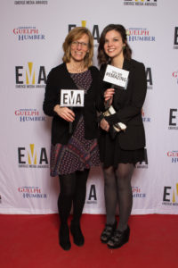 """Two ladies dressed business casual on red carpet holding small signs that read """"EMA"""" and """"You are #EMAZING"""""""