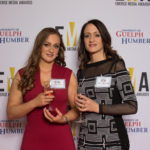 Two ladies dressed business casual on red carpet holding wine glasses