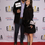 "Young couple dressed business casual on red carpet holding small signs that read ""EMA"" and ""You are #EMAZING"""
