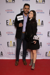 """Young couple dressed business casual on red carpet holding small signs that read """"EMA"""" and """"You are #EMAZING"""""""