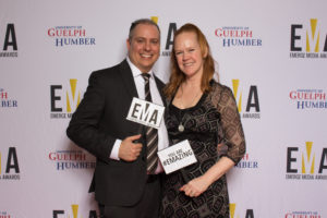 "Two people dressed business casual on red carpet holding small signs that read ""EMA"" and ""You are #EMAZING"""