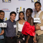 "Group of young people dressed business casual on red carpet holding small signs that read ""EMA"" and ""You are #EMAZING"""