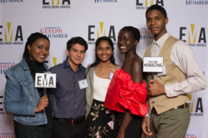 """Group of young people dressed business casual on red carpet holding small signs that read """"EMA"""" and """"You are #EMAZING"""""""