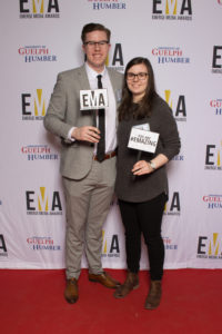 """Two people dressed business casual on red carpet holding small signs that read """"EMA"""" and """"You are #EMAZING"""""""