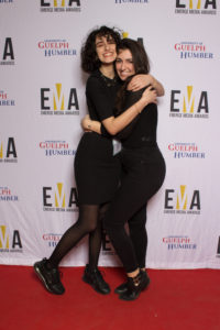 Two young ladies dressed business casual on red carpet, hugging