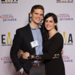 Two young people dressed business casual on red carpet, huggin