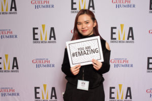"Young lady dressed business casual on red carpet holding a small sign that reads""You are #EMAZING"""