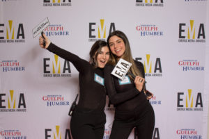 """Two young ladies dressed business casual on red carpet holding small signs that read """"EMA"""" and """"You are #EMAZING"""""""