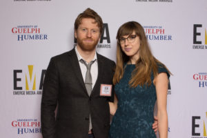 Two young people dressed business casual on red carpet