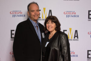 Two people dressed business casual on red carpet