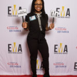 "One young lady dressed business casual on red carpet holding small signs that read ""EMA"" and ""You are #EMAZING"""