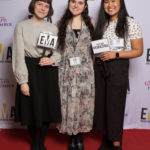 "Three young ladies dressed business casual on red carpet holding small signs that read ""EMA"" and ""You are #EMAZING"""