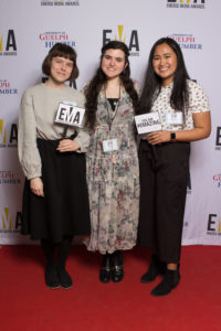 """Three young ladies dressed business casual on red carpet holding small signs that read """"EMA"""" and """"You are #EMAZING"""""""