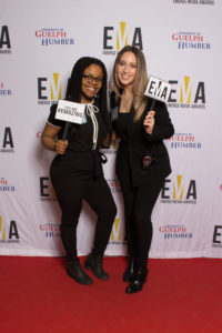 "Two young ladies dressed business casual on red carpet holding small signs that read ""EMA"" and ""You are #EMAZING"""