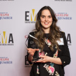 One lady dressed business casual on red carpet holding an EMA award