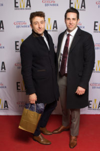 Two young men dressed business casual on red carpet