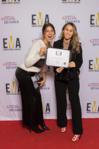 Two young ladies dressed business casual on red carpet holding the EMA certificate
