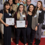 Group of people dressed business casual on red carpet holding an EMA award and certificates