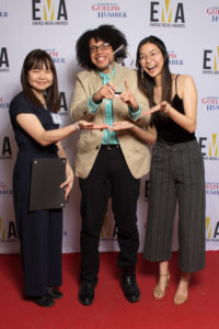Three people dressed business casual on red carpet holding an EMA award