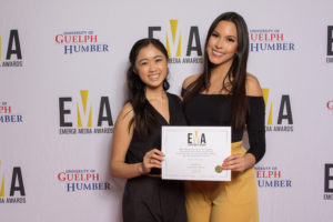 Two ladies dressed business casual on red carpet holding EMA certificate