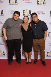 Three young people dressed business casual on red carpet