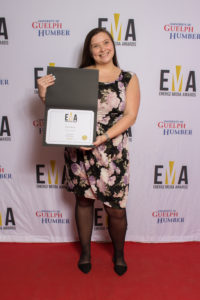 One lady dressed business casual on red carpet holding an EMA certificate