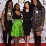 Four young people dressed business casual on red carpet