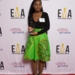 One lady people dressed business casual on red carpet holding an EMA award