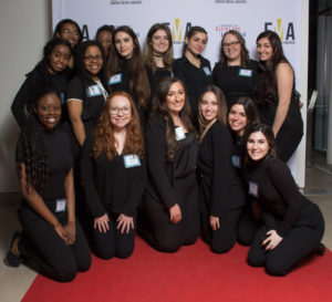 Group of young people dressed business casual on red carpet