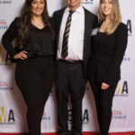 Three people dressed business casual on red carpet