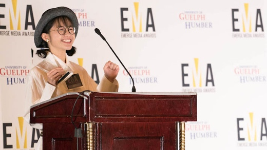 A young woman excitedly accepts her Emerge Media Award